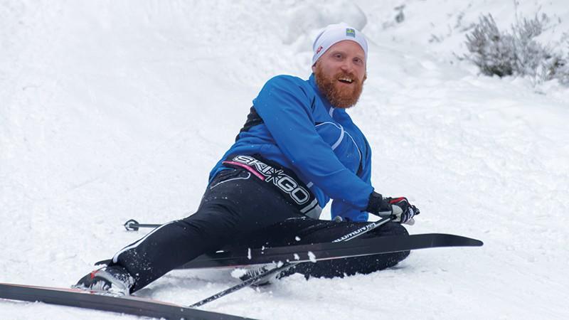 Langläufer sitzt im Schnee und lächelt