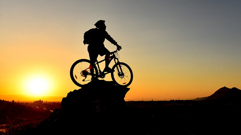 Mann steht mit dem Mountain-Bike auf dem Berg beim Sonnenuntergang